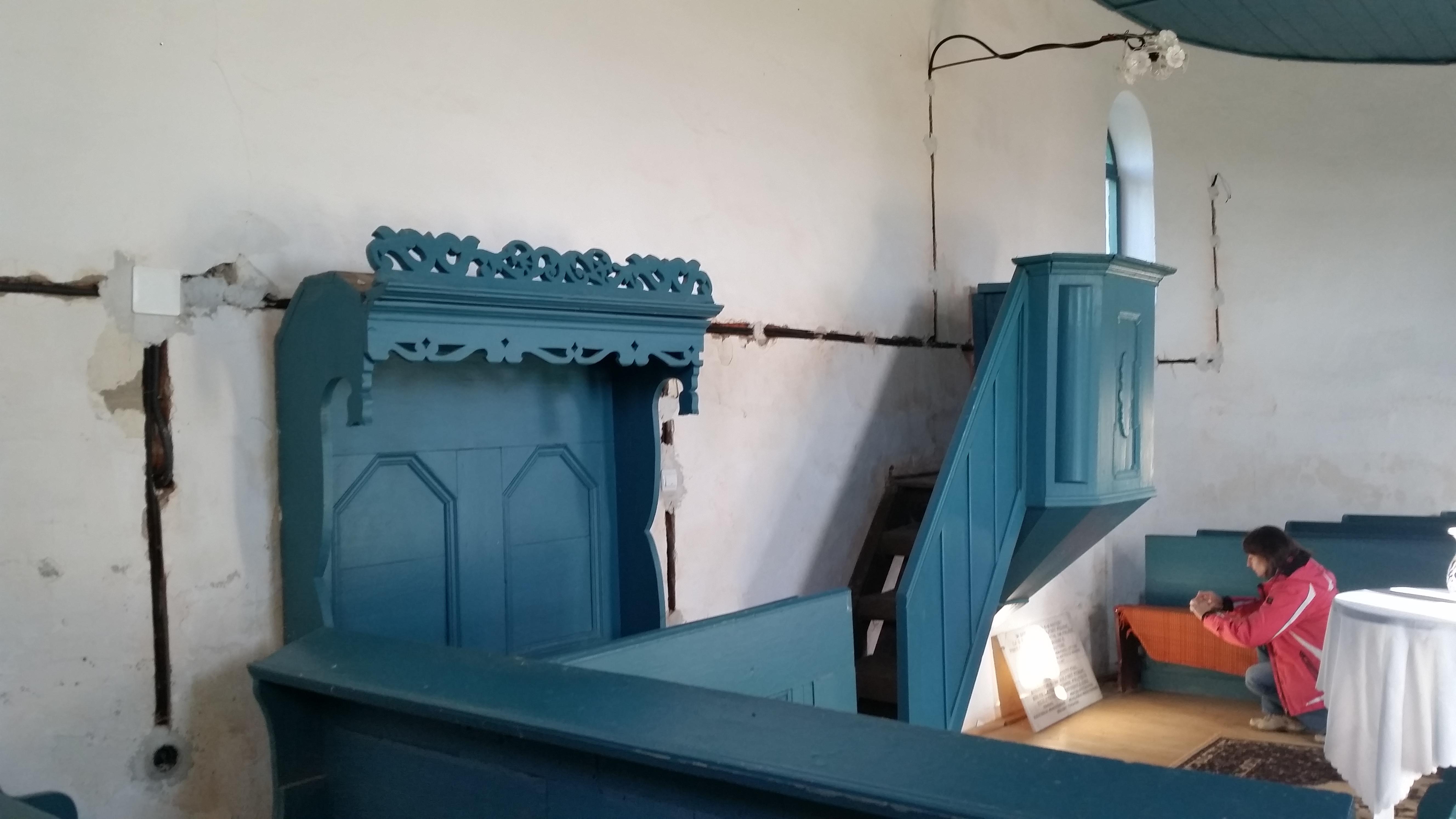 Papi szék és szószék, alatta a korábban itt elhelyezett kétnyelvű emléktáblával