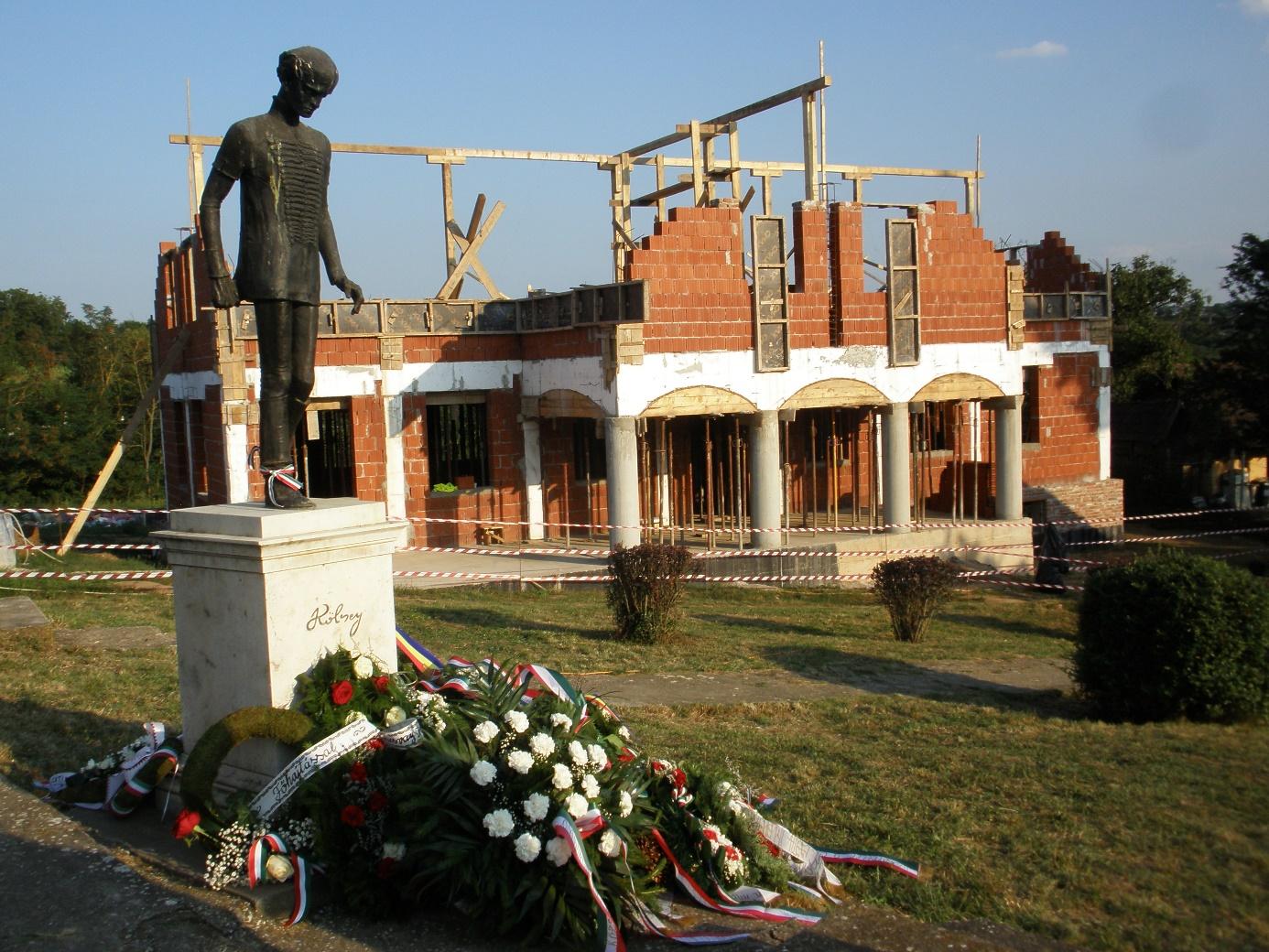 Koszorúk Kölcsey szobránál, háttérben az épülő Kölcsey Emlékház